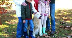 Familia que se coloca en el parque con su perro almacen de metraje de vídeo