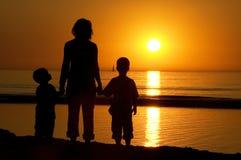 Familia que se coloca en la playa Imágenes de archivo libres de regalías