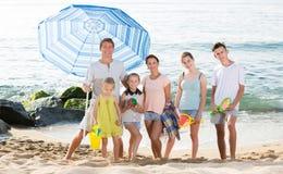 Familia que se coloca en la playa arenosa Fotografía de archivo libre de regalías
