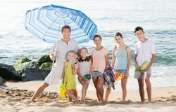 Familia que se coloca en la playa arenosa Imágenes de archivo libres de regalías