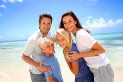Familia que se coloca en una playa hermosa Foto de archivo