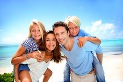 Familia que se coloca en una playa hermosa Imagen de archivo