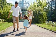 Familia que se divierte al aire libre Padres jovenes felices, el jugar de los niños imagen de archivo