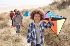 Familia que se divierte con la cometa en dunas de arena Fotografía de archivo libre de regalías
