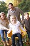 Familia que se divierte con las hojas de otoño en jardín Imagenes de archivo
