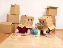 Familia que se divierte el desempaquetar en su nuevo hogar Imágenes de archivo libres de regalías