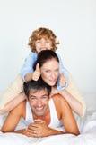 Familia que se divierte en cama con los pulgares para arriba Imágenes de archivo libres de regalías