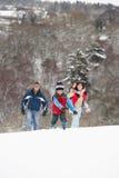 Familia que se divierte en el campo Nevado Imagen de archivo libre de regalías
