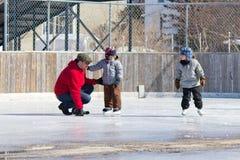 Familia que se divierte en la pista de patinaje Imagen de archivo libre de regalías