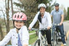 Familia que se divierte en las bicis imagen de archivo libre de regalías