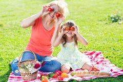Familia que se divierte mientras que merienda en el campo en el parque Fotos de archivo libres de regalías