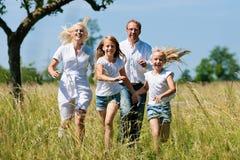 Familia que se ejecuta en el prado Imagen de archivo libre de regalías