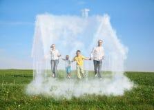 Familia que se ejecuta en hierba y casa ideal Foto de archivo