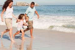 Familia que se ejecuta en la playa Foto de archivo libre de regalías