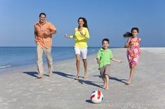 Familia que se ejecuta en la playa con la bola del balompié Foto de archivo libre de regalías