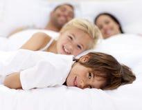 Familia que se reclina en la cama del padre Fotos de archivo