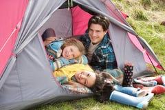 Familia que se relaja dentro de la tienda en acampada imágenes de archivo libres de regalías