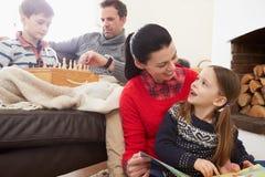 Familia que se relaja dentro jugando el libro del ajedrez y de lectura Imágenes de archivo libres de regalías