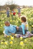 Familia que se relaja en el campo de los narcisos del resorte Imagenes de archivo