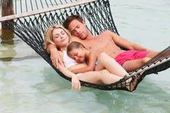 Familia que se relaja en hamaca de la playa Imagen de archivo