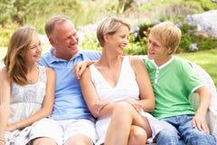 Familia que se relaja en jardín Imágenes de archivo libres de regalías
