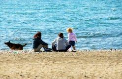 Familia que se relaja en la playa Imagenes de archivo