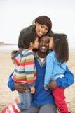 Familia que se relaja en rotura de la playa del invierno Imagen de archivo