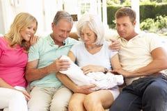 Familia que se relaja junto en el sofá con el bebé recién nacido Imagen de archivo libre de regalías