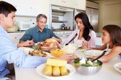 Familia que se sienta alrededor de la tabla que dice rezo antes de comer la comida Fotos de archivo