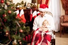Familia que se sienta alrededor del árbol de navidad Papá y bebé en el Ne Imagen de archivo libre de regalías