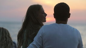 Familia que se sienta cerca del mar en la puesta del sol, el marido almacen de metraje de vídeo