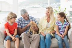 Familia que se sienta con el gato en el sofá en casa Imagen de archivo