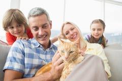 Familia que se sienta con el gato en el sofá en casa Imágenes de archivo libres de regalías