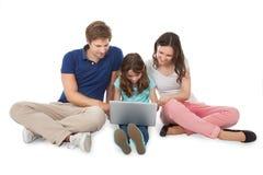Familia que se sienta con el ordenador portátil sobre el fondo blanco Foto de archivo