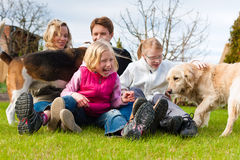 Familia que se sienta con los perros junto en un prado Imagen de archivo