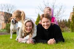 Familia que se sienta con los perros junto en un prado Foto de archivo libre de regalías