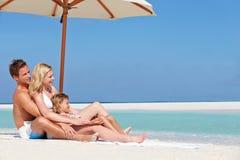 Familia que se sienta debajo del paraguas el día de fiesta de la playa Imagenes de archivo