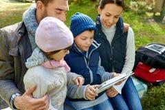 Familia que se sienta en banco con PC de la tableta en el campo imágenes de archivo libres de regalías