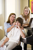 Familia que se sienta en banco del piano, hijo de tomadura de pelo de la madre Fotografía de archivo libre de regalías
