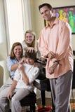 Familia que se sienta en banco del piano, hijo de tomadura de pelo de la madre Imagen de archivo