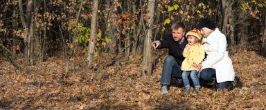 Familia que se sienta en bosque y Live Nature de observación Imagenes de archivo