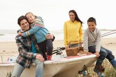 Familia que se sienta en el barco con la pesca Rod en la playa Fotografía de archivo libre de regalías