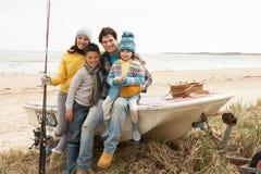 Familia que se sienta en el barco con la pesca Rod en la playa Foto de archivo libre de regalías