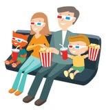 Familia que se sienta en el cine y que mira una película Foto de archivo
