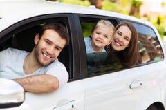 Familia que se sienta en el coche que mira hacia fuera ventanas Fotos de archivo libres de regalías