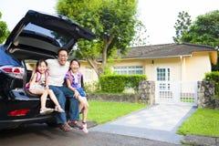 Familia que se sienta en el coche y su casa detrás Fotos de archivo libres de regalías