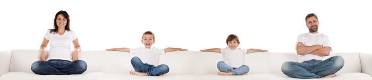 Familia que se sienta en el sofá blanco imagen de archivo libre de regalías