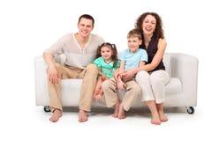 Familia que se sienta en el sofá del cuero blanco Fotografía de archivo