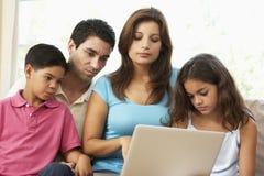 Familia que se sienta en el sofá en el país con la computadora portátil Imagenes de archivo