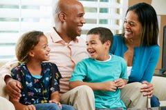 Familia que se sienta en el sofá junto foto de archivo